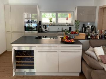 Küche mit Senosan Hochglanz-Front, Arbeitsplatte aus Dekton, gelederte Oberfläche. Ein besonderer Hingucker ist der integrierte Weinkühlschrank.