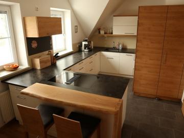 Einbauküche in weiß kombiniert mit Asteiche furniert mit Frühstücksbar in Asteiche massiv.  Granitplatte geledert, Induktions-Muldenlüfter