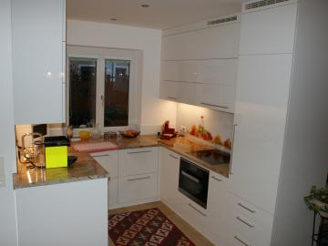 Küche U-Form, Front Hochglanz, Arbeitsplatte Granit Praha Gold und Lacobel Glasrückwand.