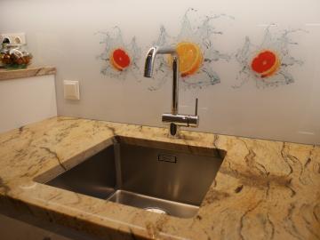 Granit-Arbeitsplatte mit Unterbauspüle, Oberfläche poliert; individuell bedruckte Glasrückwand