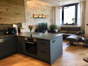 Küche matt lackiert mit Anti-Fingerprint-Beschichtung kombiniert mit Crackeiche, Arbeitsplatte und Küchenrückwand Granit geledert