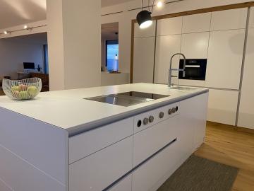 Küche mit Kochinsel und Griffleiste,  Schleiflackoberfläche, Dekton Arbeitsplatte, integriertes BORA-System