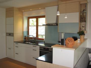 Küche aus Dekorspanplatte mit Silestone Arbeitsplatte geledert und Lacobel Glasrückwand.