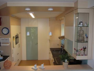 Küche aus Dekorspanplatte mit Speistrennwand und flächenbündiger Tür.