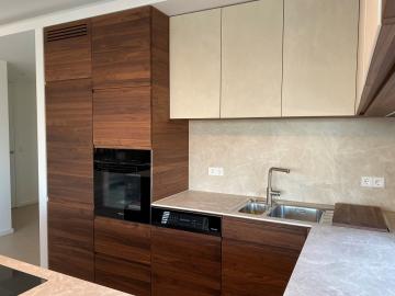 Eine moderne Kombination aus massivem Nussbaum und Keramik. Massive Holzfronten mit Grifffräsung.