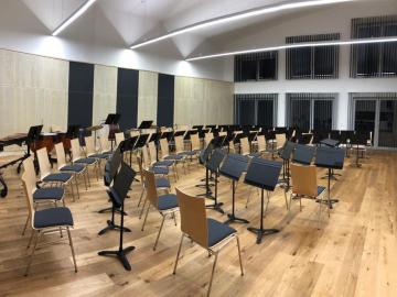 Orchesterproberaum mit Akustikpaneelen aus Holz für Wand und Decke. Integrierte Stauraummöbel mit gelochten Akustik-Schrankfronten Ahorn furniert.