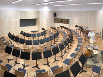 Orchesterproberaum mit Wand und Decken Akustikpaneelen. Integrierte Stauraummöbel mit gelochten Akustik-Fronten Ahorn furniert.