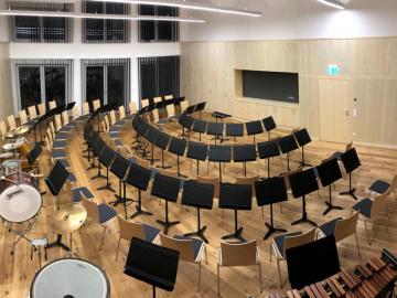 Orchesterproberaum mit Wand und Decken Akustikpaneelen aus Holz. Integrierte Stauraummöbel Ahorn furniert mit gelochten Akustik-Fronten.