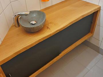 Waschbeckenunterschrank in Eiche massiv mit Baumkante, Schiebetür aus Rohstahl, Aufsatzbecken aus Granit