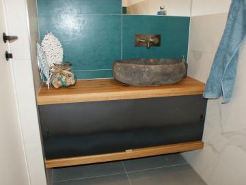 Waschtischunterbau in Eiche mit Schiebetür aus Rohstahl und Naturstein Aufsatzbecken