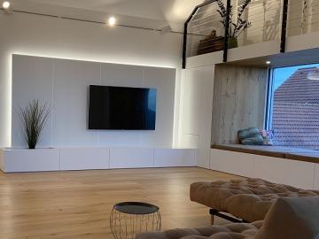 Wand mit Akustikpaneelen perforiert, Oberfläche weiß lackiert, Ladenauszüge grifflos, integr. Blumenwanne und LED-Beleuchung